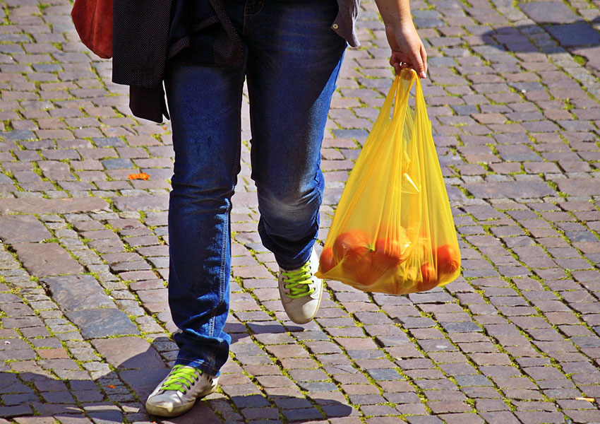 Persona caminando con bolsas de plástico