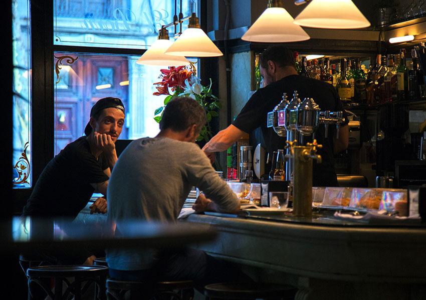 Hombres sentados en bar de tapas